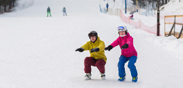 two people at ski resort crouching at the bottom of a hill