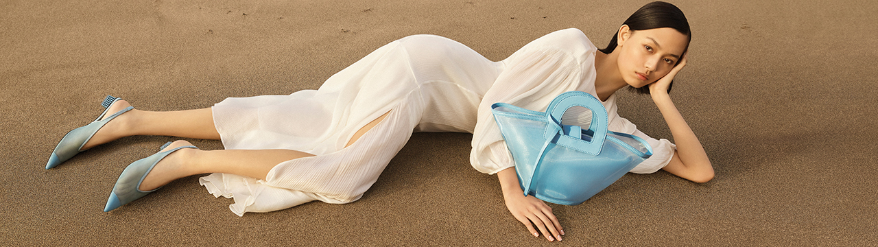 asian lady lying down on sand wearing clothes and accessories from charles & keith