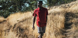 man wearing a red shirt and hiking in a field