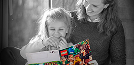 woman and daughter looking at a lego magazine