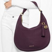 michael kors model wearing all white and a purple handbag