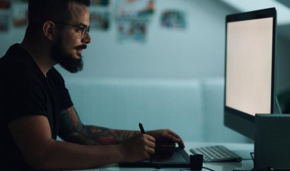 man using a drawing pad at computer