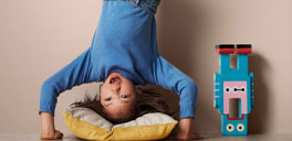 kid upside down on a pillow with an upside down toy
