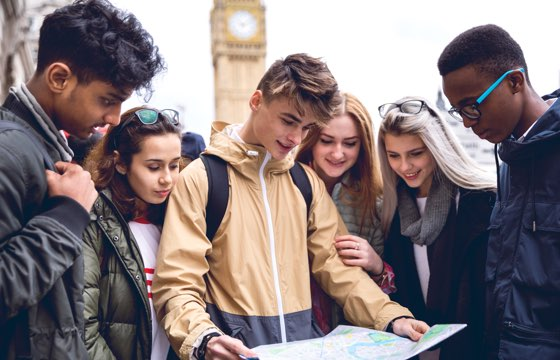 Young people looking at a map while on holiday in London. Big Ben visible in background.