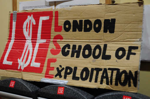 "Cardboard sign with handpainted text, ""LSE - London School of Exploitation"""