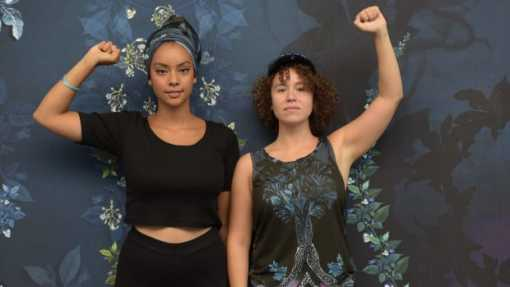 Two women lifting up their fist