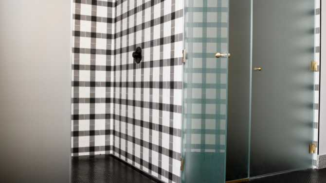 Two spacious showers with black and white tile and frosted glass doors.