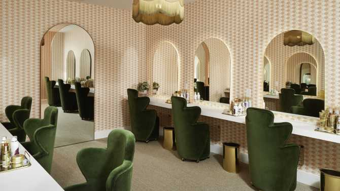 A photo of the beauty room at The Wing Bryant Park featuring green velvet chairs, mirrors, and pink patterned wallpaper