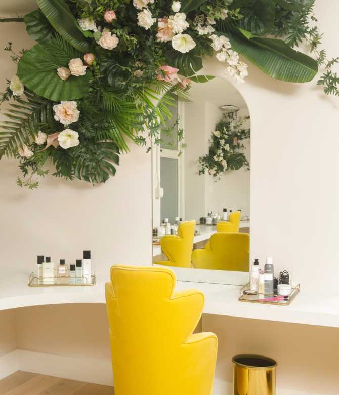 Long desk with mirror, bright yellow chair and jungle-like plants above.