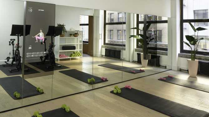 Image of fitness room with yoga mats, mirrors, and cycling bikes