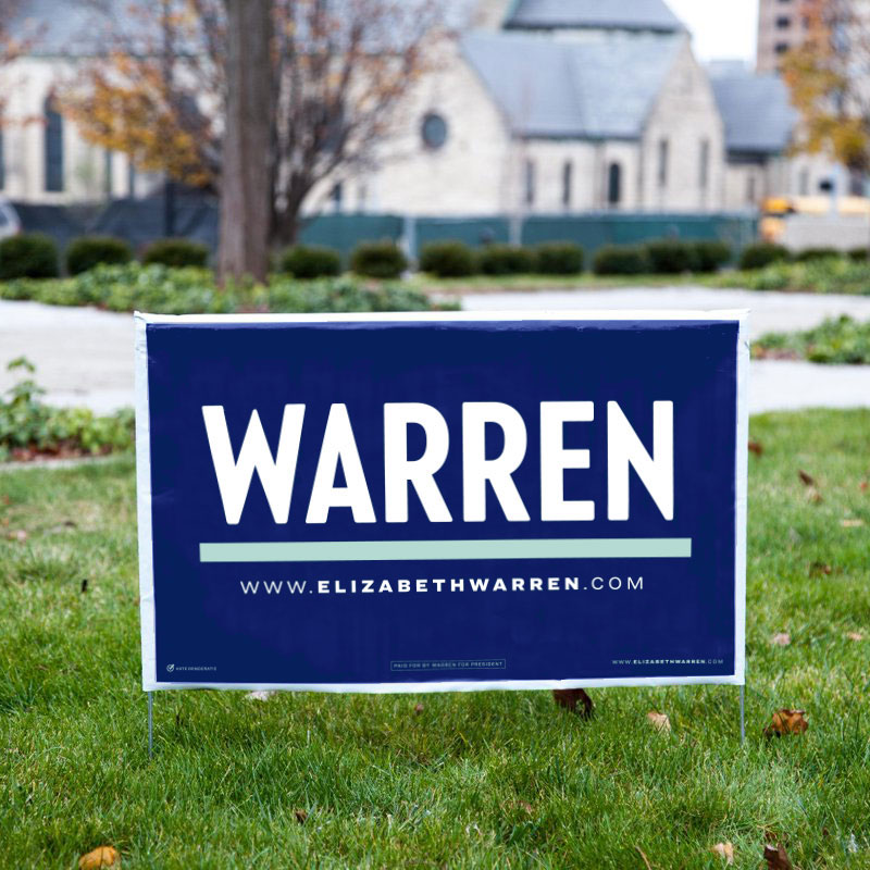 "Navy blue yard sign in a grassy yard with ""WARREN"" logo in white with a liberty green underline and www.elizabethwarren.com under the line"