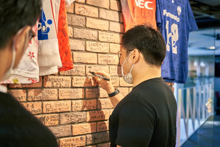 壁にメッセージを書く川村選手