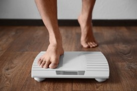 Man stepping onto scales - weight loss can help to treat type 2 diabetes