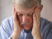 Man with diabetes has hands over his face, as to indicate burnout