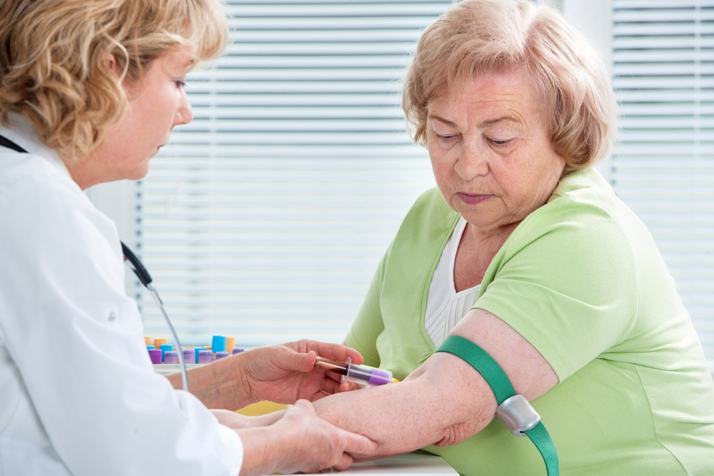 nurse conducts blood test to test HbA1c of elderly lady with diabetes