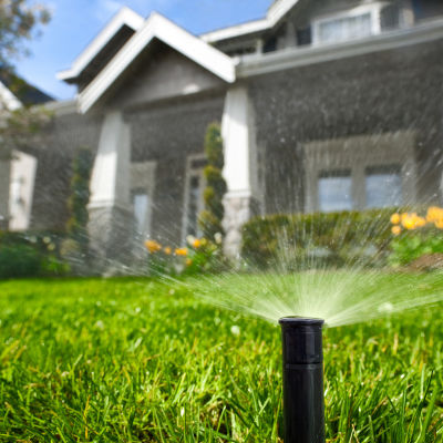 sprinkler system spraying water in front yard
