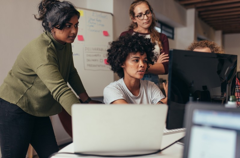 A group of women in front of a computer looking at a computer screen