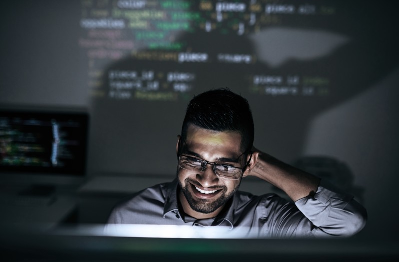 A guy standing in front of code projected on a wall