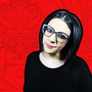 A headshot of Salma wearing black on a red patterned background.