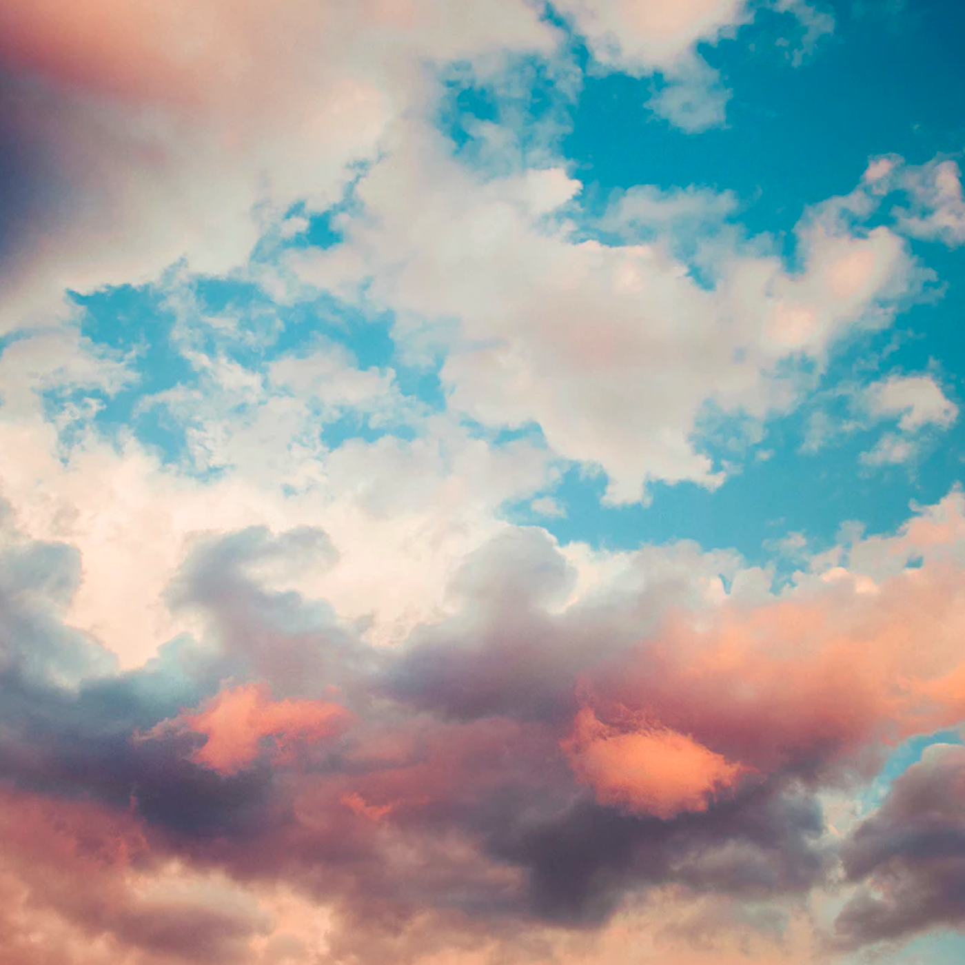 A photo of white and red clouds against a dark blue sky