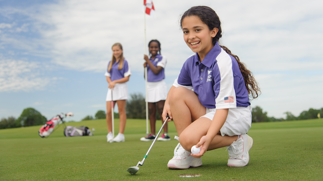 Three junior girls on golf green
