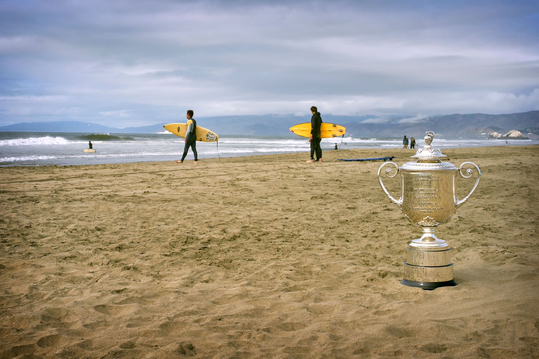 The Wanamaker Trophy sits on the beach as surfers head out to ride the waves of the Pacific Ocean.