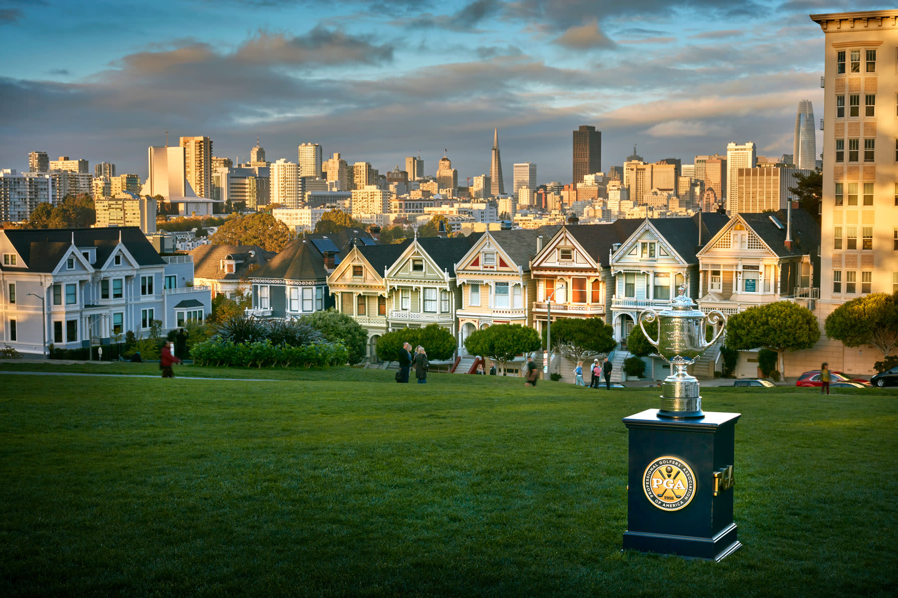 "The Wanamaker Trophy in Alamo Square park with the famous ""Painted Ladies"" row of houses in the background."