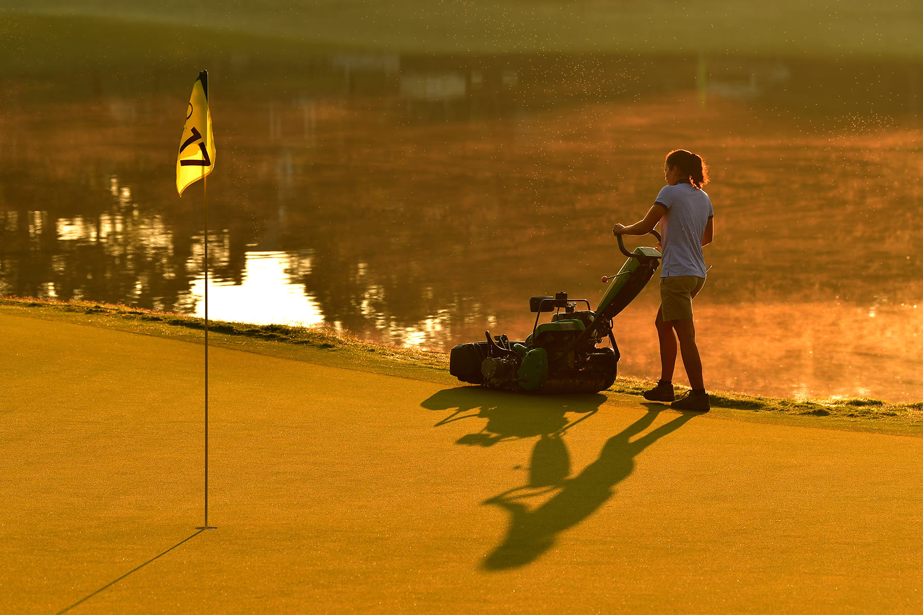 A grounds crew worker prepares the course on the 17th green during the first round of the 2017 PGA Championship at Quail Hollow Club on August 10, 2017 in Charlotte, North Carolina.