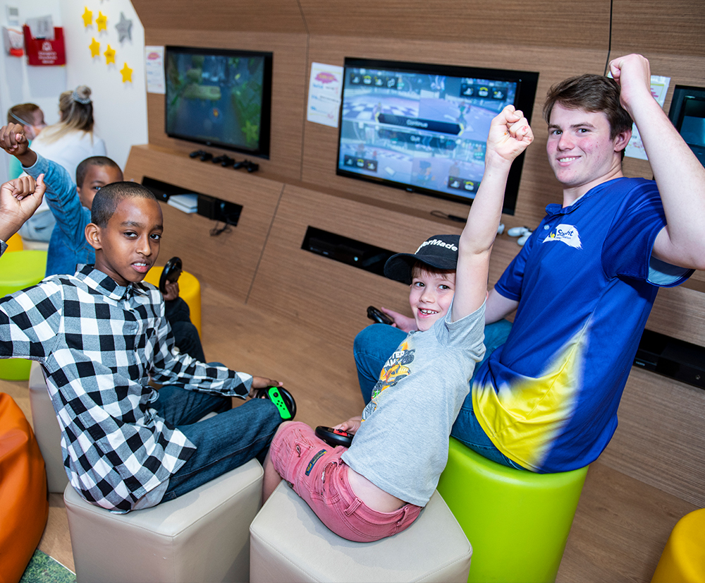 Male volunteer in the Starlight Express Room playing video games with kids