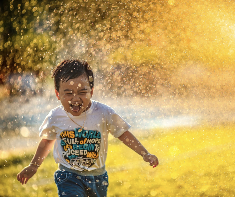 Child running in a water sprinkler