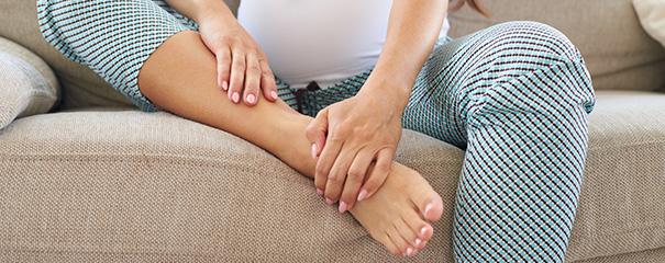Futura mamá aliviando sus tobillos hinchados y doloridos