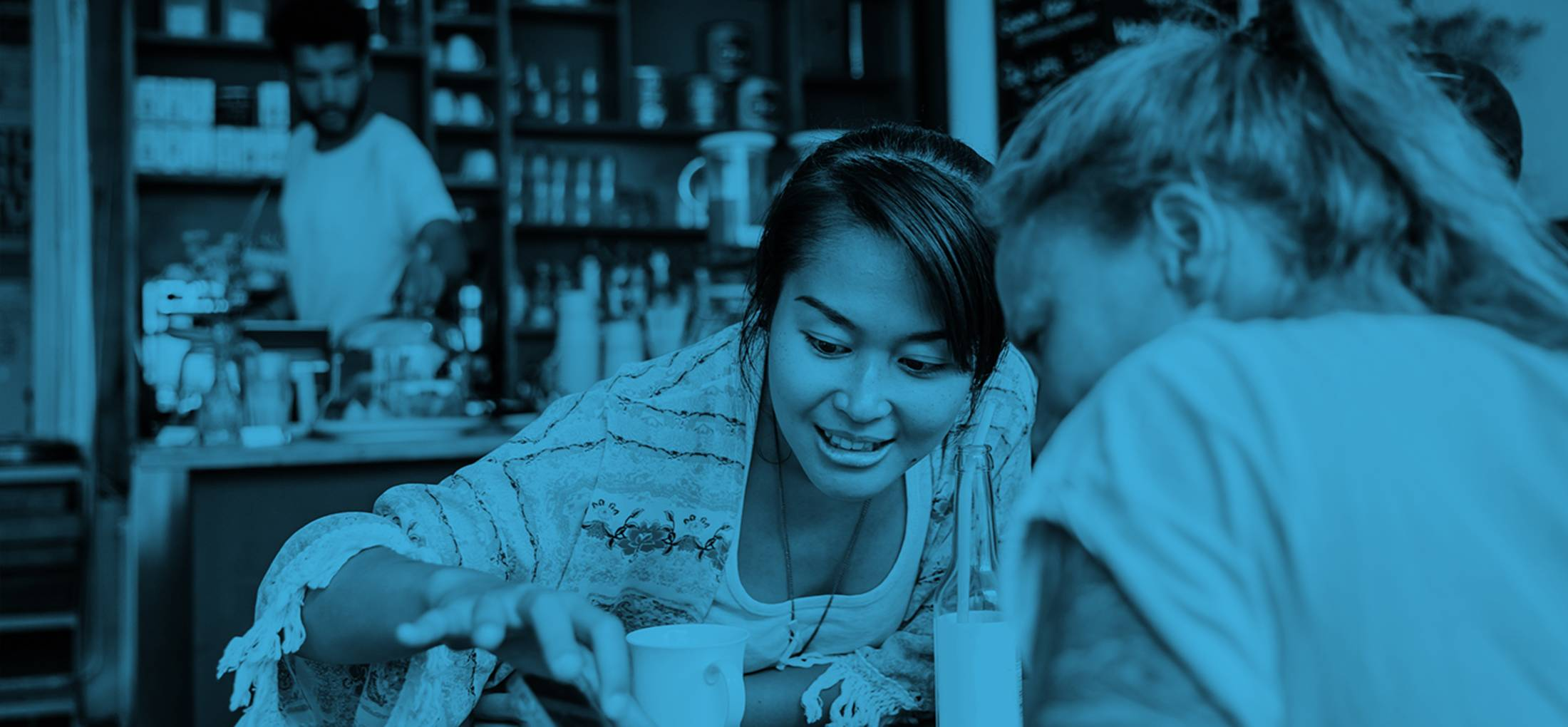 Two women at a cafe looking at a mobile phone