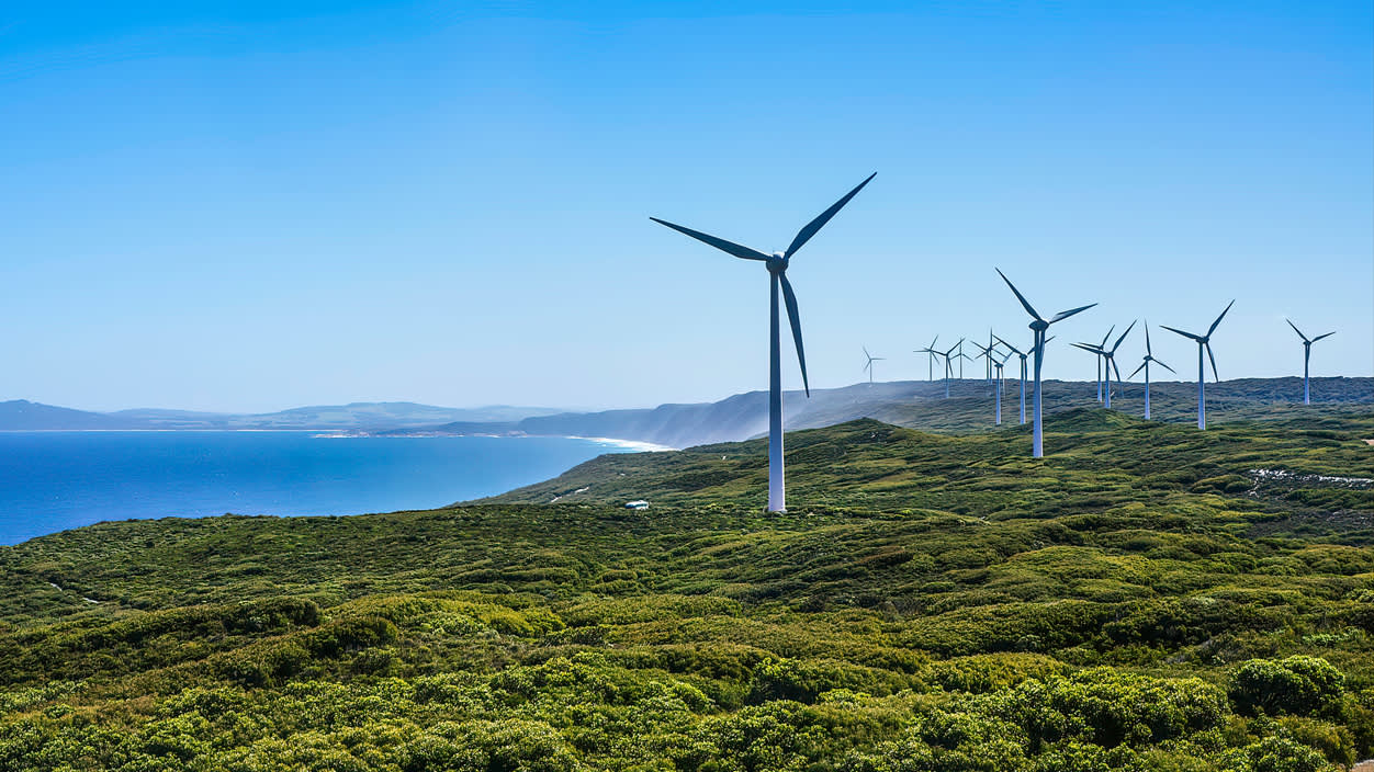 Wind turbines overlooking the coast on a sunny day