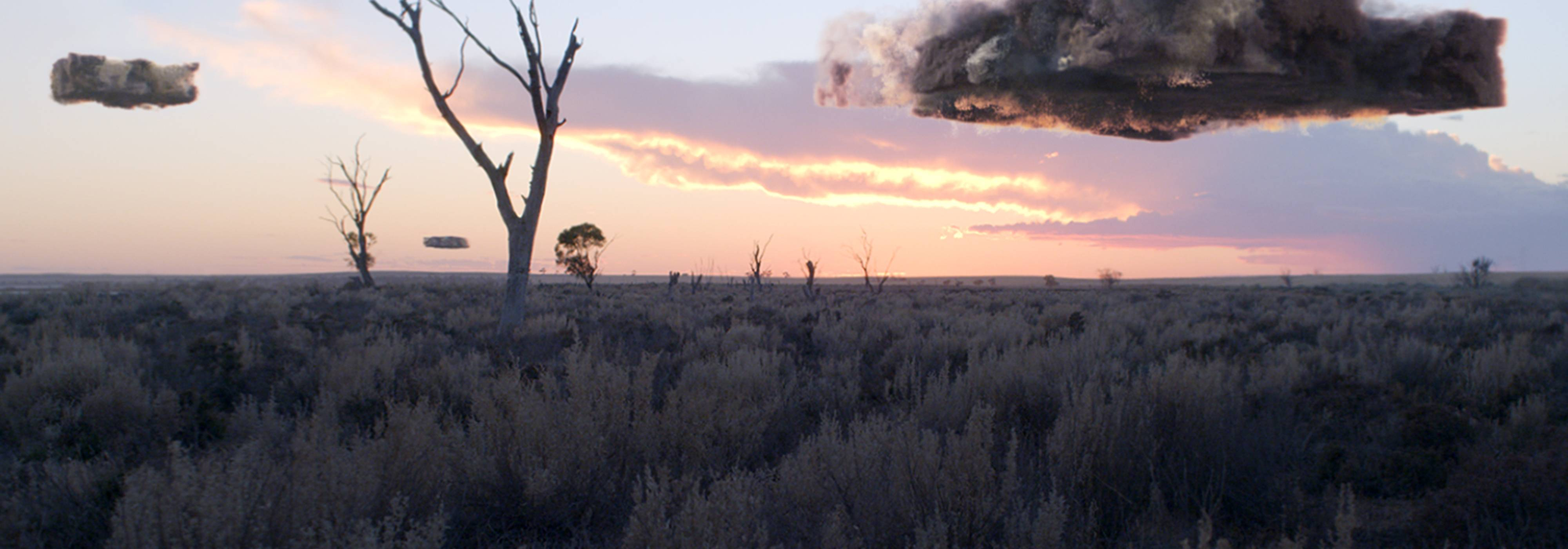 Square-shaped chunks of air pollution above a grassy outback landscape at sunrise.