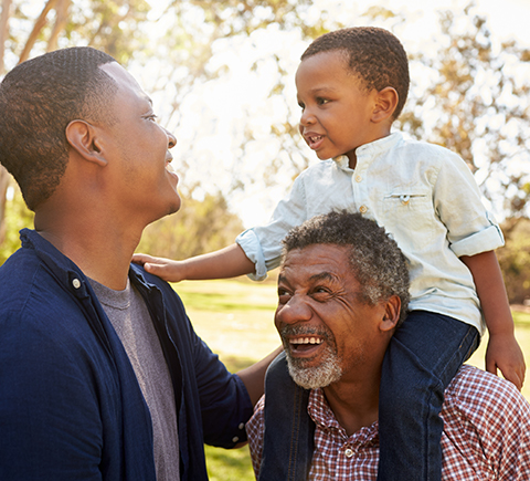 A multigenerational family smiling at each other.