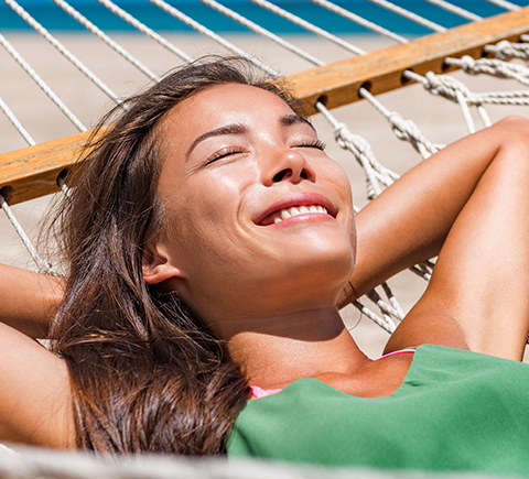 a woman sunbathing on a hammock