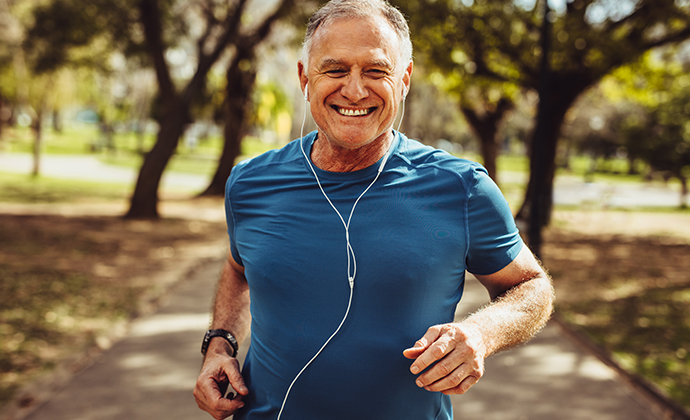 A picture of a man running outside with headphones.