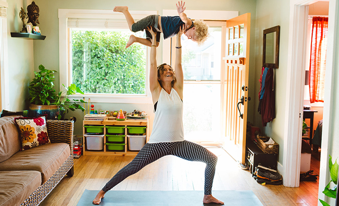 A mother carrying her young child while working out at home.