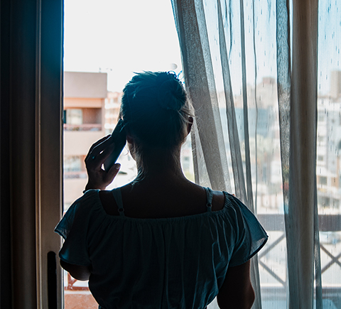 An image of a woman on the phone looking out on her balcony.