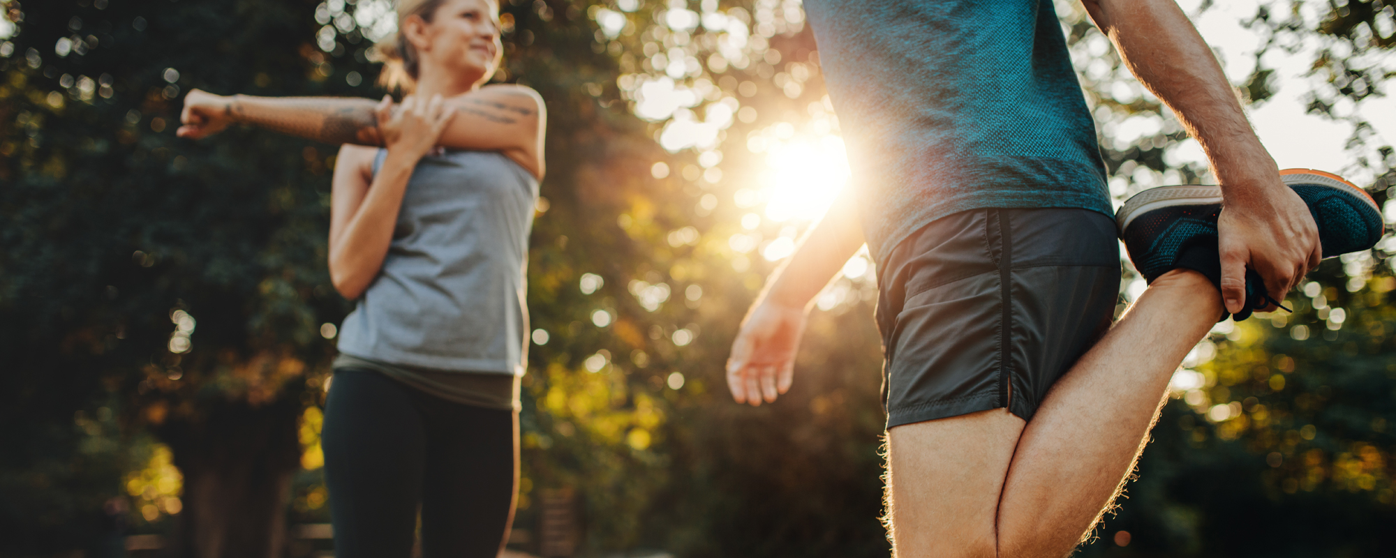 Two joggers stretching outside before a run.