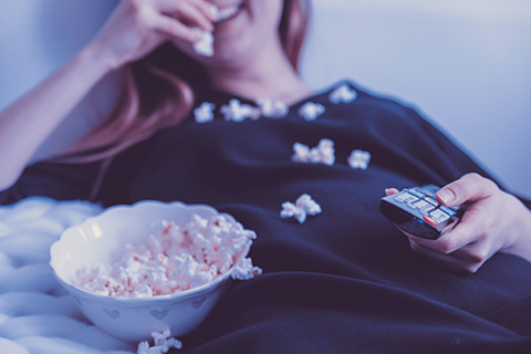 An image of a person laying down on their couch, eating popcorn, and watching television.