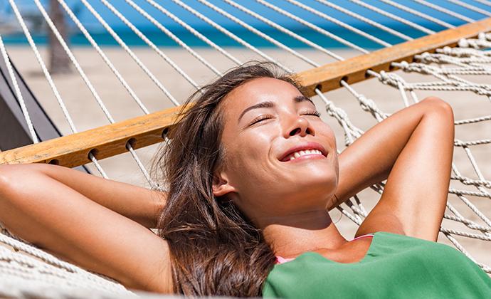 a woman sunbathing on a hammock