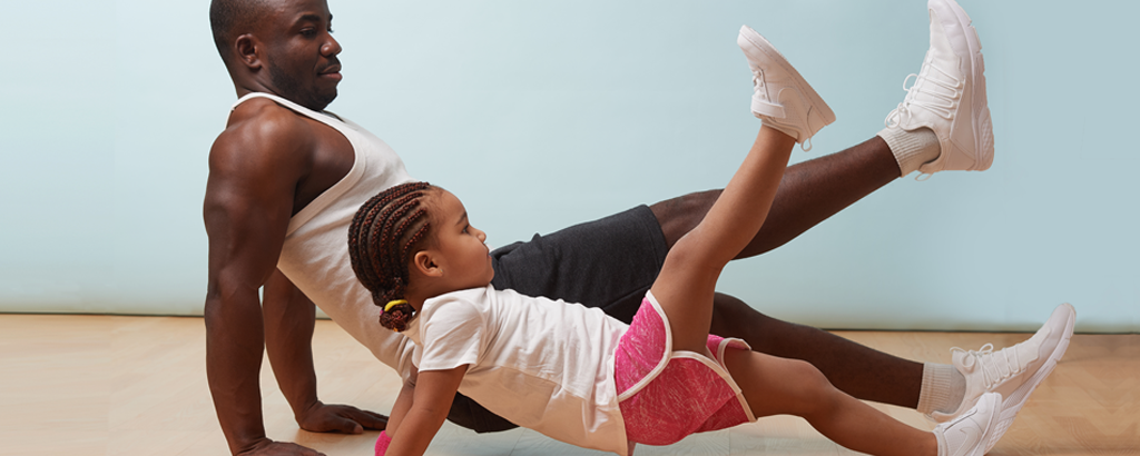 Father and daughter doing leg raises