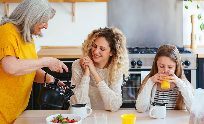 A stay at home mother pouring coffee and orange juice for her daughters.