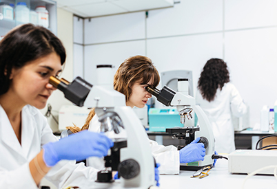 scientists looking through a microscope in a lab