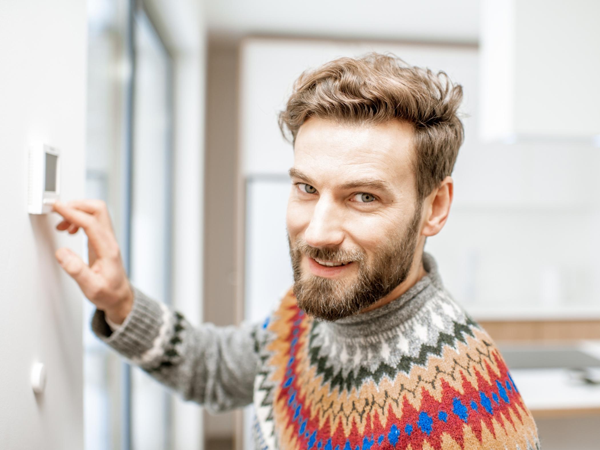 Man at home adjusting thermostat