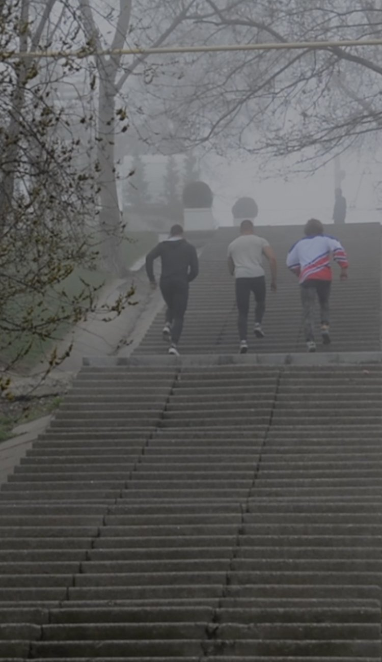 Three men running up park steps.