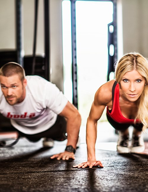 Chris and Heidi Powell doing pushups.