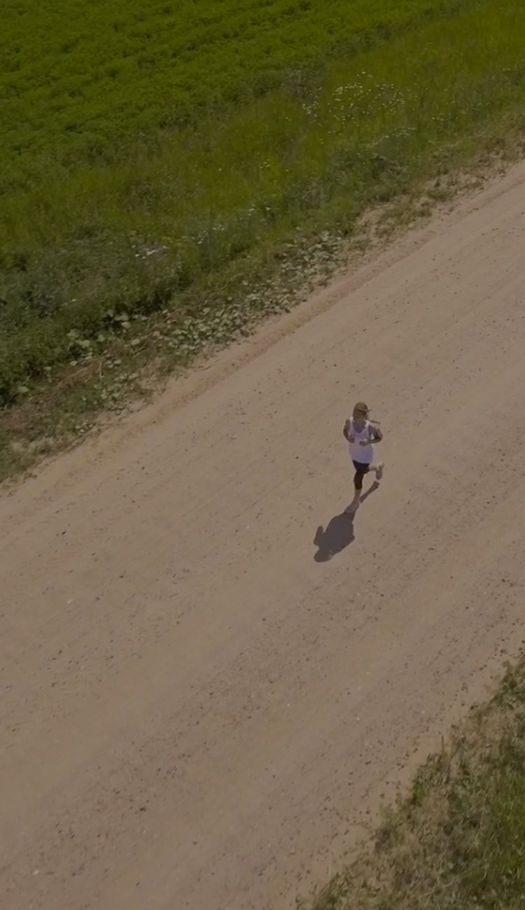 Aerial photo of a woman running on a dirt road.