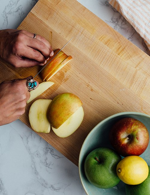 Image of a woman cutting fresh apples on wooden board.